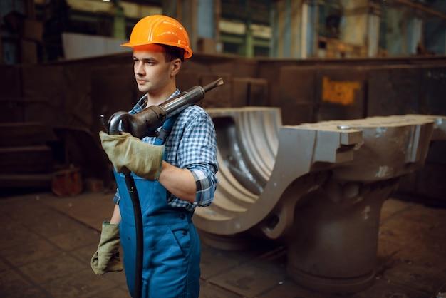 Männlicher arbeiter in uniform und helm hält pneumatischen presslufthammer in der fabrik. metallverarbeitende industrie, industrielle herstellung von stahlprodukten