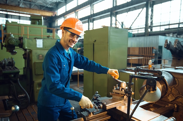 Männlicher arbeiter in uniform und helm überprüft drehbank auf werk
