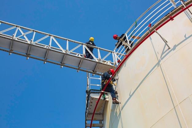 Männlicher arbeiter industrieller seilzugangsschweißer, der in der höhe mit gurtzeug, helmsicherheitsausrüstung seilzugangsinspektion der dickenlagertankindustrie arbeitet.