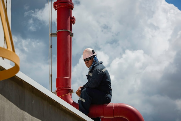 Männlicher arbeiter inspektion visueller pipeline lagertank ölhintergrund und blauer himmel.