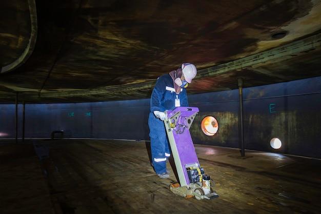 Männlicher arbeiter inspektionsboden scannen tank externes schwimmen der rostwand verlieren dicke bodenplatte in zu begrenzt