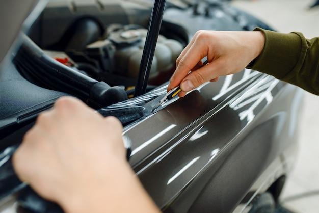 Männlicher arbeiter installiert transparente schutzfolie auf der motorhaube. anbringen einer beschichtung, die den lack des autos vor kratzern schützt. neufahrzeug in garage, tuning