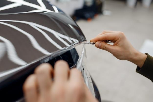 Männlicher arbeiter installiert transparente schutzfolie auf der motorhaube. installation einer beschichtung, die den lack des automobils vor kratzern schützt. neues fahrzeug in der garage