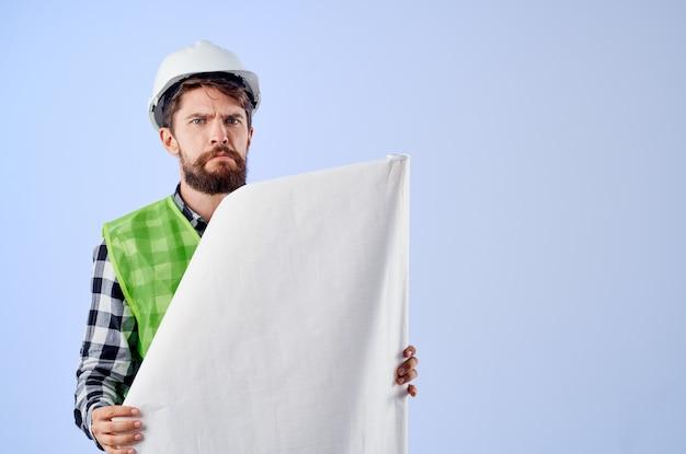 Männlicher arbeiter mit dokumenten und zeichnungen blaupausen blauem hintergrund