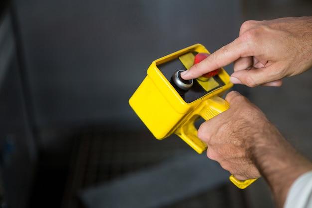 Männlicher arbeiter mit gelbem werkzeug in der fabrik