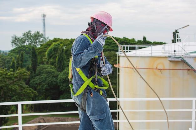 Männlicher arbeiter mit sicherheitsgurt und sicherheitsleine, der an einem hohen handlauf auf offenem tankdachöl arbeitet