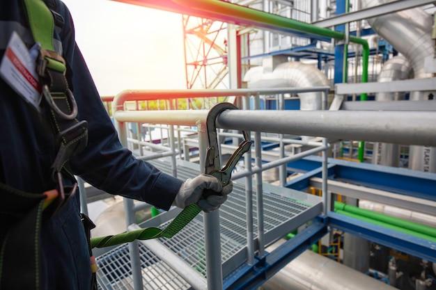 Männlicher arbeiter mit sicherheitsgurthaken und sicherheitsleinenhandlauf, der an hoher stelle arbeitet