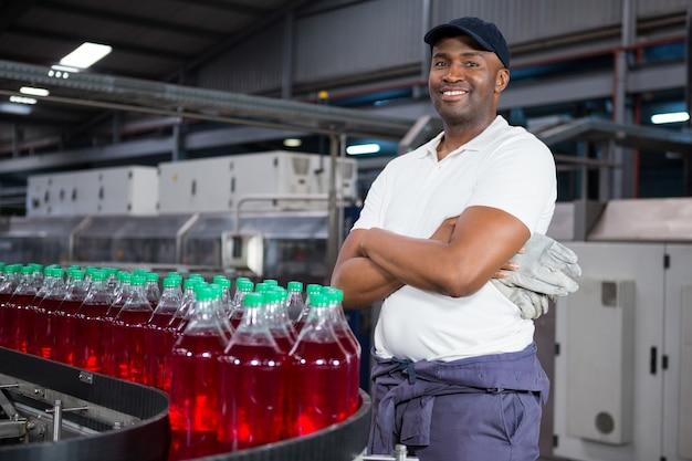 Männlicher arbeiter mit verschränkten armen, die durch flaschen auf produktionslinie in der fabrik stehen
