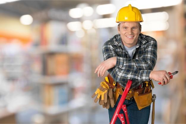 Männlicher arbeiter mit werkzeuggürtel auf hintergrund isoliert