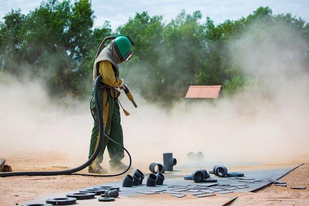 Männlicher arbeiter sandstrahlverfahren reinigung der rohrleitungsoberfläche auf stahl vor dem lackieren in der fabrik.