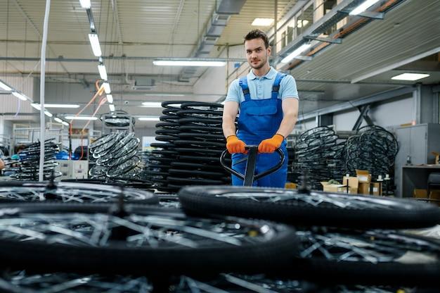 Männlicher arbeiter trägt fahrradräder auf einem wagen in der fabrik. montagelinie für fahrradfelgen in der werkstatt, installation von fahrradteilen, moderne technologie