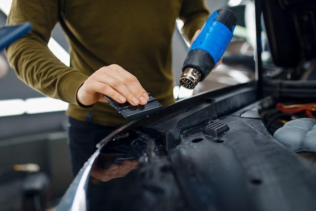 Männlicher arbeiter trocknet vinyl-autoschutzfolie auf der motorhaube. anbringen einer beschichtung, die den lack des autos vor kratzern schützt. neufahrzeug in garage, tuning-vorgang