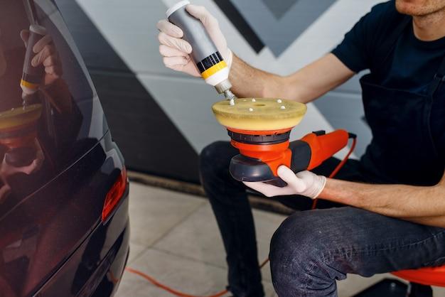 Männlicher arbeiter wendet politur auf poliermaschine, autodetaillierung an. vorbereitung vor dem anbringen der beschichtung, die den autolack vor kratzern schützt. fahrzeug in garage, autotuning