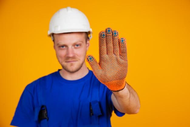 Männlicher arbeiter zeigt stop-hand-geste. arbeiter in overalls und schutzhelm zeigt stopphandbewegung mit behandschuhter hand