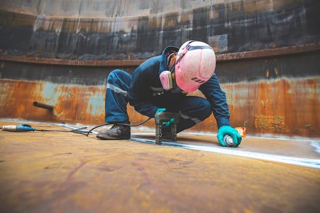 Männlicher arbeitertest stahltank stumpfschweißung kohlenstoffbodenplatte des lagertanks ölhintergrund weißer kontrast des magnetfeldtests