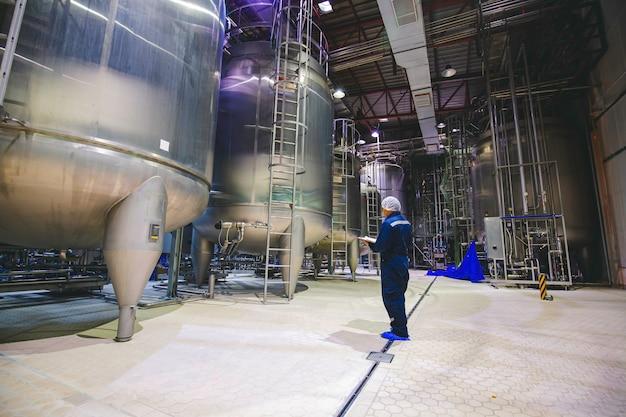Männlicher arbeitsinspektionsprozess milchpulverkeller in der fabrik mit vertikalen edelstahltanks