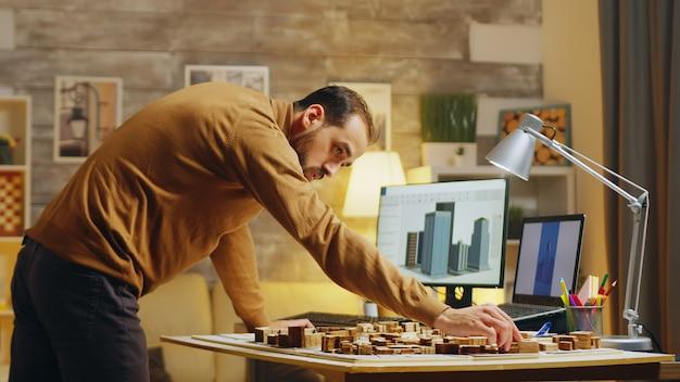 Männlicher architekt, der am computer tippt, während er an einem projekt für die stadtentwicklung arbeitet.