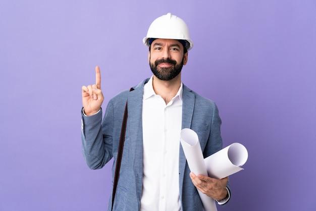 Männlicher architekt, der mit helm aufwirft und nach oben zeigt