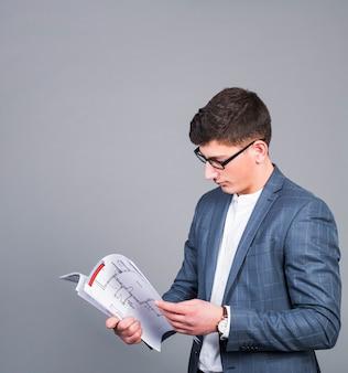 Männlicher architekt, der papier mit projekt betrachtet