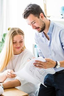 Männlicher architekt, der seinem weiblichen kollegen plan zeigt