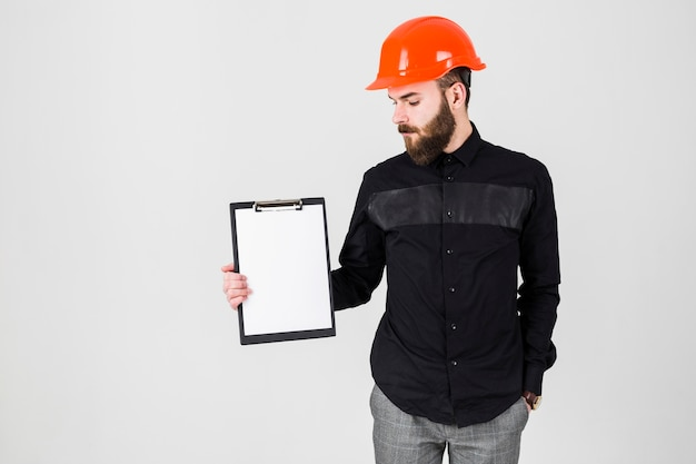 Männlicher architekt, der weißbuch auf klemmbrett betrachtet
