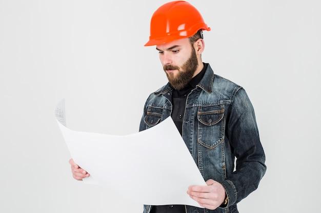 Männlicher architekt, der weißen plan gegen weißen hintergrund betrachtet