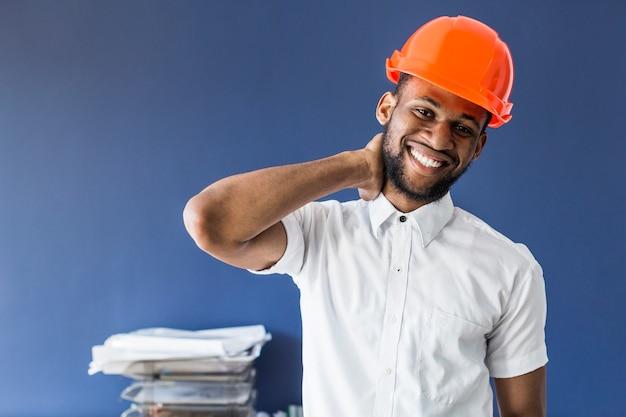 Männlicher architekt des afroamerikaners, der gegen blaue wand am arbeitsplatz steht