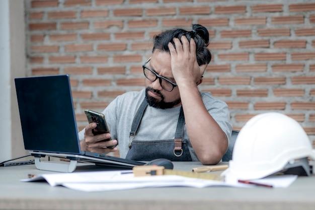 Männlicher architekt oder ingenieur, der zu hause arbeitet und auf sein telefon schaut