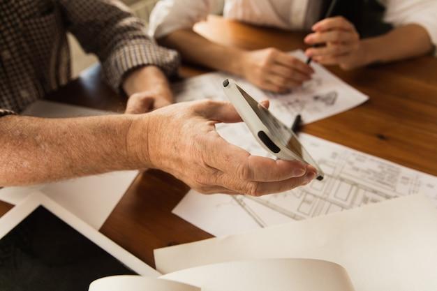 Männlicher architekt präsentiert projekt des zukünftigen hauses für junge familie