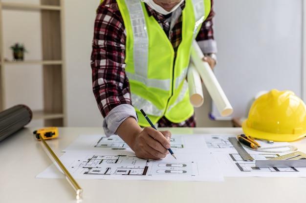Männlicher architekt schreibt auf die hauspläne, er überprüft die von ihm entworfenen hauspläne, bevor er sie an die kunden schickt, er entwirft das haus und die inneneinrichtung. ideen für die wohngestaltung.