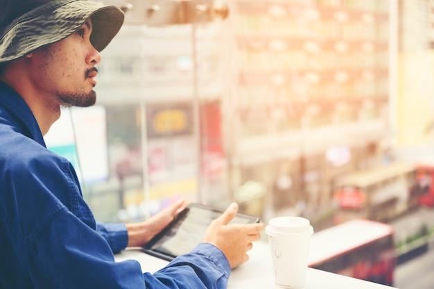 Männlicher architekt with digital tablet, das pläne im büro studiert