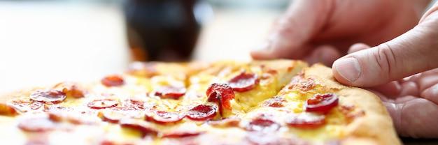 Männlicher arm, der scheibe der käsigen leckeren frischen pizza nimmt