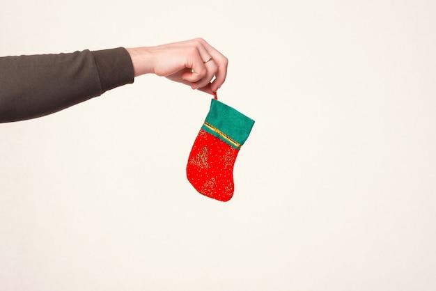 Männlicher arm hält eine hängende weihnachtssocke über weißem hintergrund.