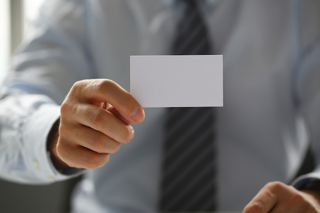 Männlicher arm im anzug, der eine leere visitenkarte zur besuchernahaufnahme hält.