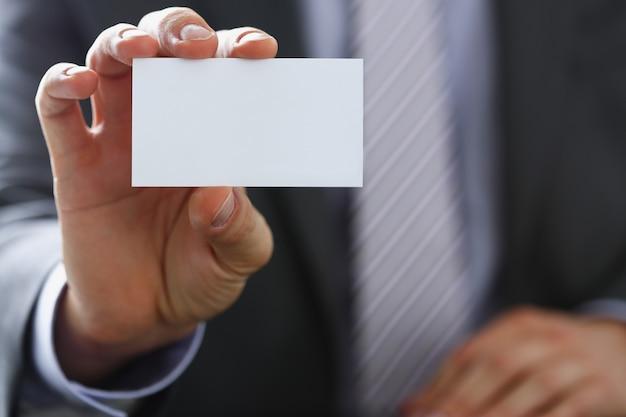 Männlicher arm im anzug geben leere visitenkarte