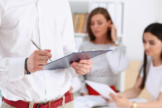 Männlicher arm im büro, das arbeitsvertragsformular auf klemmbrettauflage mit silberner stiftnahaufnahme liest und unterzeichnet. schlagen sie ein unternehmensverkaufs-versicherungsagentkonzept der übereinkaufsentscheidungs-büro-motivation
