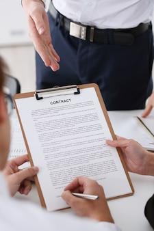 Männlicher arm im hemdangebotvertragsformular auf klemmbrettauflage und silberstift, zum der nahaufnahme zu unterzeichnen. schlagen sie ein übereinkommen für unternehmensverkaufs-versicherungsagentkonzept der wirtschaftskragenmotivations-gewerkschaftsentscheidung