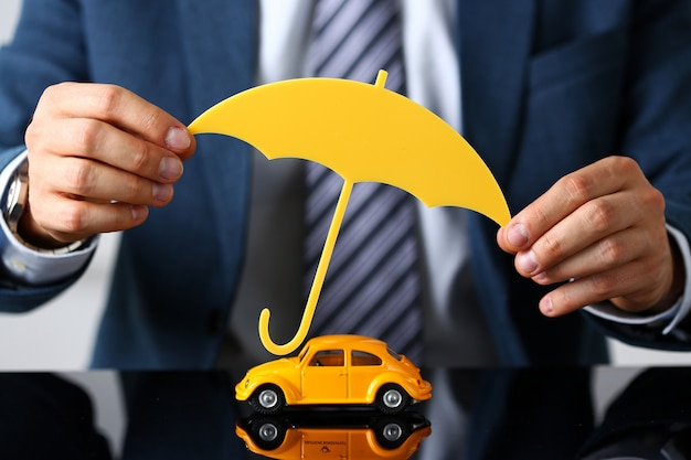 Männlicher arm in anzug und krawatte bedeckt ein gelbes spielzeugauto