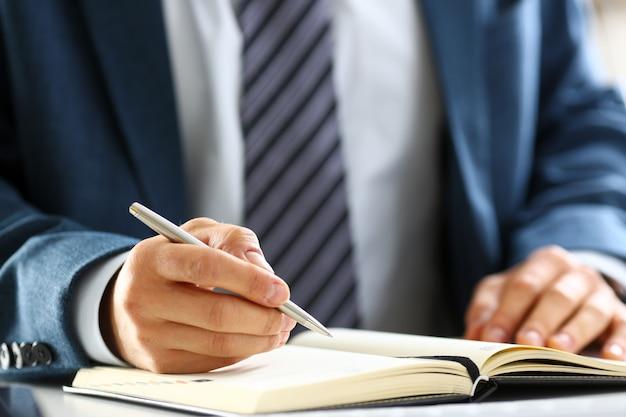 Männlicher arm in anzug und krawatte halten silbernen stift