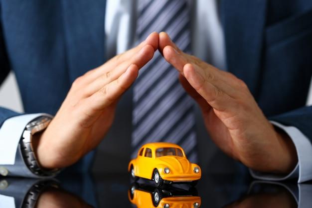 Männlicher arm in anzug und krawattenabdeckung gelbes spielzeugauto