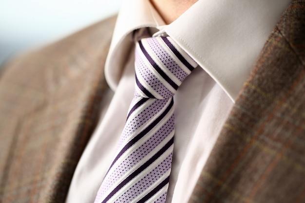 Männlicher arm in der gesetzten bindungsnahaufnahme des braunen anzugs