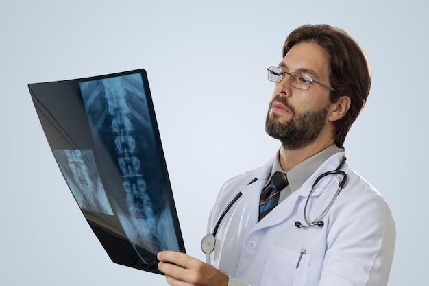 Männlicher arzt auf einer grauen wand, die eine röntgenaufnahme betrachtet