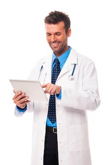 Männlicher arzt, der an digitaler tablette arbeitet