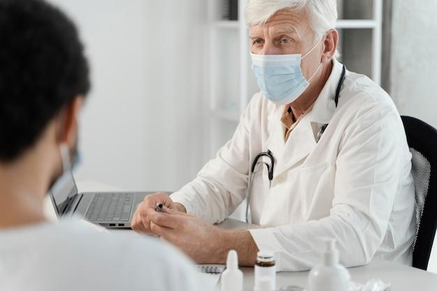 Männlicher arzt, der dem patienten medikamente verschreibt