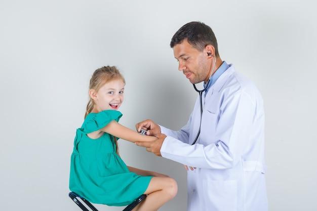 Männlicher arzt, der den arm des kleinen mädchens mit stethoskop in der weißen einheitlichen vorderansicht untersucht.