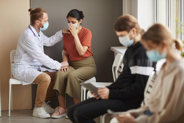 Männlicher arzt, der die patientin unterstützt, während sie weint, dass sie mit anderen menschen im korridor des krankenhauses sitzt