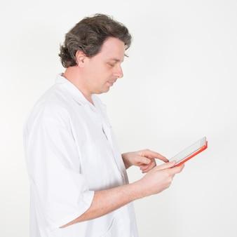 Männlicher arzt, der digitales tablett auf weiß verwendet