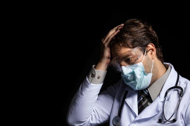 Männlicher arzt, der eine maske und eine schutzbrille trägt, müde von der arbeit mit covid-19 auf einem schwarzen hintergrund.