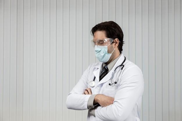 Männlicher arzt, der eine maske und eine schutzbrille trägt, müde von der arbeit mit covid-19 auf einem weißen hintergrund.