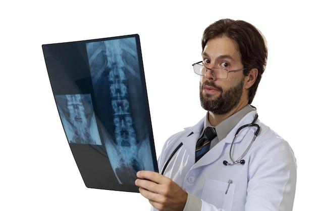 Männlicher arzt, der eine röntgenaufnahme auf einem weißen raum betrachtet.